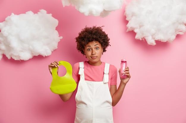 Zwangerschap, moederschap, verwachting concept. zwangere vrouw houdt zuigfles met tepel en slabbetje, bereidt zich voor om moeder te worden, draagt witte sarafan, geïsoleerd op roze muur met wolken