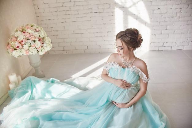 Zwangerschap, vrouw zittend op de vloer in een luxe jurk en hand in hand over haar buik. de vrouw wacht op de geboorte van een baby. liefhebbende vrouw