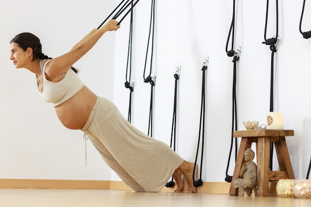 Zwangerschapsyoga jonge vrouw beoefent yoga thuis