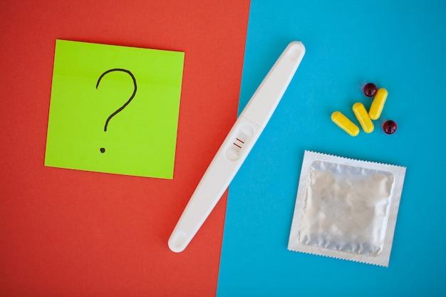 Zwangerschaptest. het resultaat is positief met twee strips en condoom met voorbehoedsmiddel, anticonceptiepil, veilig vrijen, gezondheidszorgconcept