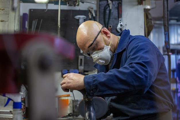 Zware industrie werknemer snijden staal met haakse slijper bij autoservice.