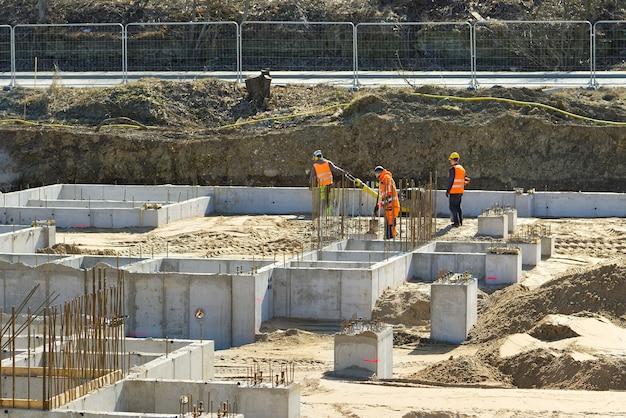 Zware machines op een bouwplaats groei van de vastgoedmarkt bouw van de fundering voor het toekomstige kantoor- en woongebouw