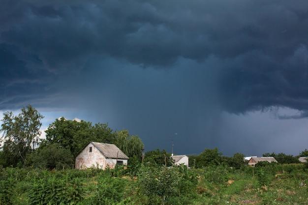 Zware regenval in de buurt van een oud verlaten huis in een ver dorp. groene natuur