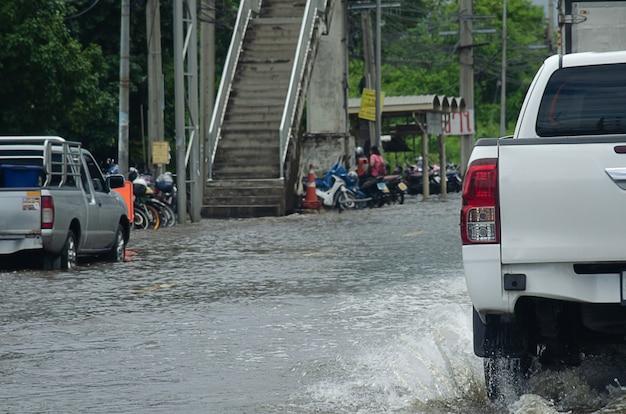 Zware regenval zet de wegen van thailand onder water. de auto rijdt door het overstroomde water.