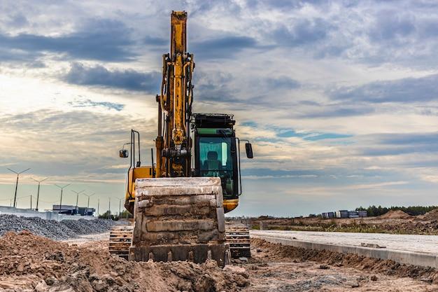 Zware rupsgraafmachine met een grote emmer op de achtergrond van de avondrood. zware bouwmachines voor grondwerken. verbetering van het grondgebied.