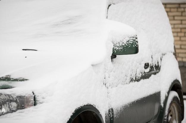 Zware sneeuwval bedekte de auto's met sneeuw op parkeerplaats naast het huis