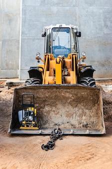 Zware voorlader op een bouwplaats met een bouwhulpmiddel in de emmer. apparatuur voor grondwerken, transport en laden van bulkmaterialen - aarde, zand, steenslag.