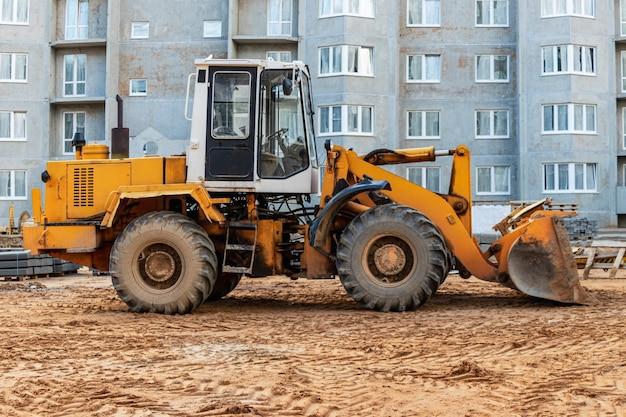 Zware wiellader met een emmer op een bouwplaats. apparatuur voor grondwerken, transport en laden van bulkmaterialen - aarde, zand, steenslag.