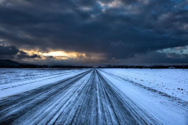 Zware zwarte wolken boven een besneeuwde weg in de winter. winter berglandschap.