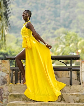 Zwart afrikaans vrouwenmodel in gele jurk Premium Foto