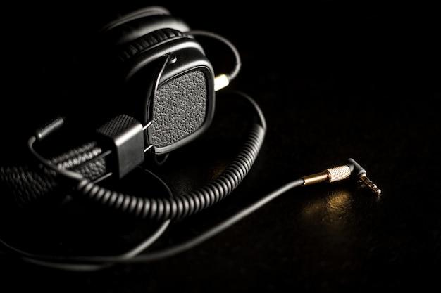 Zwart bedraad op oorhoofdtelefoons met gouden hoofdtelefoonaansluiting op donkere achtergrond
