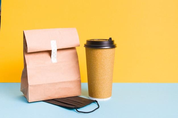 Zwart beschermend masker, kartonnen kopje koffie in gouden glanzende verpakking en papieren zak