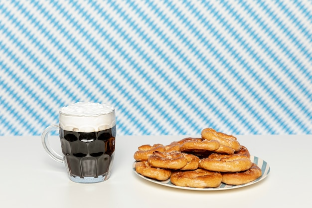 Zwart bier en zachte pretzels op witte tafel