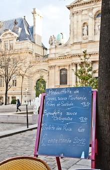 Zwart bord met een menurestaurant op een typisch traditioneel plein in parijs