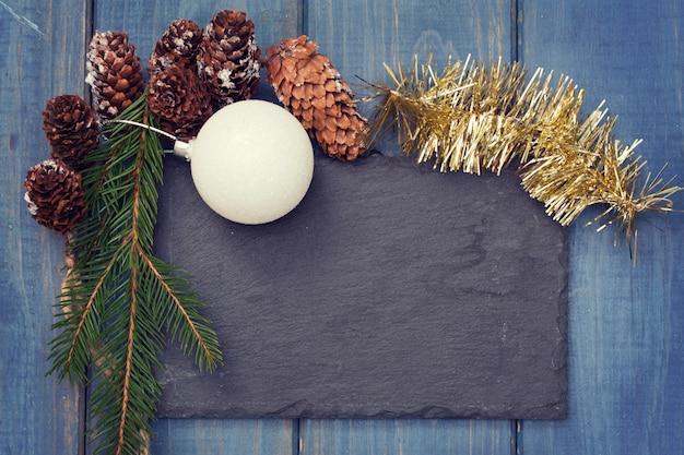 Zwart bord met kerstdecoratie op blauw hout
