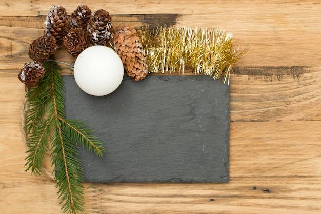 Zwart bord met kerstdecoratie op bruin hout