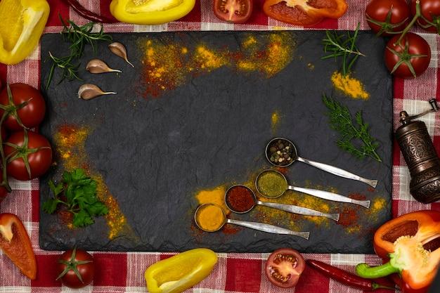 Zwart bord met verspreide kruiden, ijzeren lepels met kruiden verse groenten op een achtergrond van rode en witte stof. ruimte voor tekst. bovenaanzicht. voedsel achtergrond.