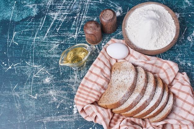 Zwart brood met ingrediënten op blauwe tafel.