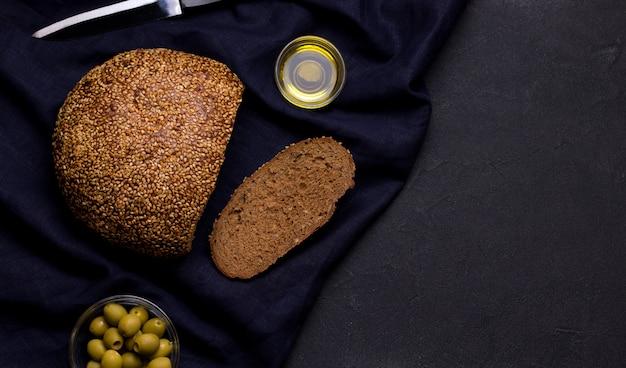 Zwart brood met sesamzaadjes op blauw linnentextiel op een zwarte ruimte. kopieer ruimte
