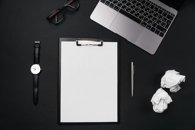 Zwart bureaudesktop met wit vel papier met gratis exemplaarruimte en pen, laptop, bril, horloge en verfrommelde papieren ballen.