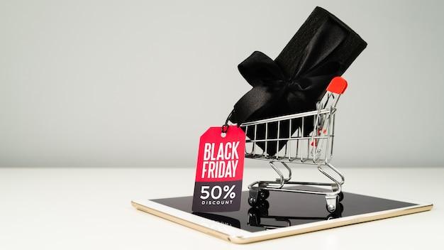 Zwart cadeau met tag in winkelwagen