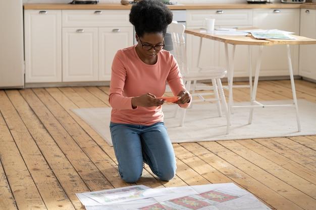 Zwart designer meisje neemt een foto van architectonisch project op mobiel zittend op de vloer thuis