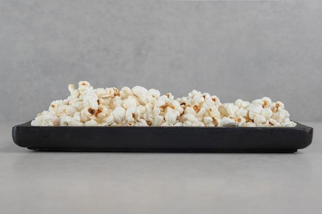 Zwart dienblad met popcorn op marmeren oppervlak.