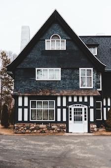 Zwart en bruin huis met drie verdiepingen dichtbij weg