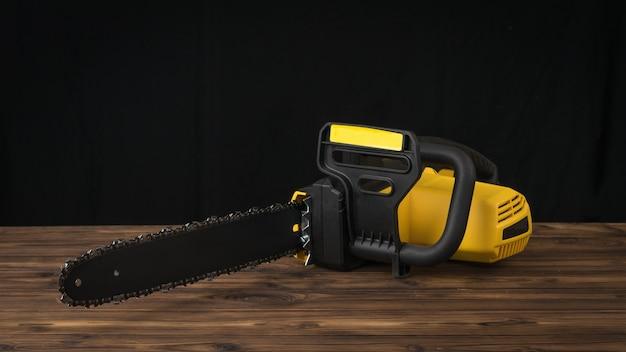 Zwart en geel elektrische zaag op een houten tafel op een zwarte achtergrond. elektrisch gereedschap voor houtverwerking.