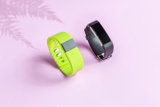 Zwart en groen fitness gezondheidshorloge met varenschaduw op lichte muur.