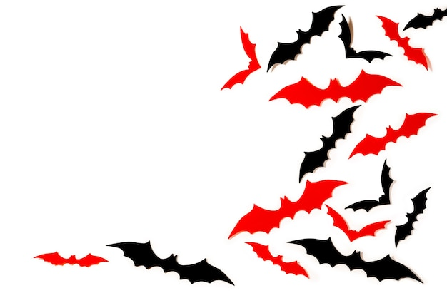 Zwart en rood papier gesneden vleermuizen vliegen over witte achtergrond. halloween-decoratieachtergrond met exemplaarruimte.