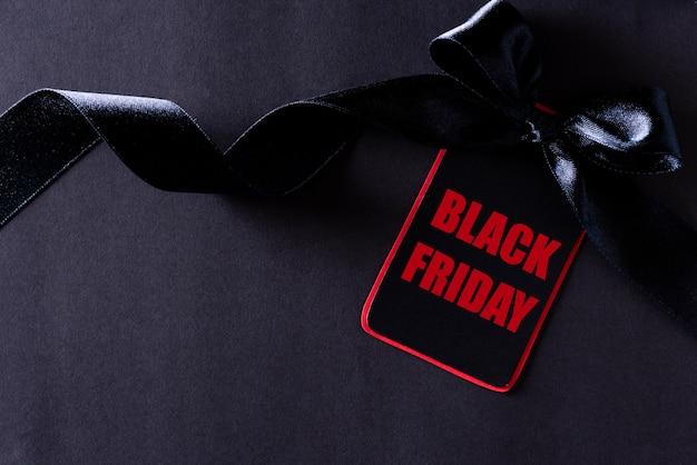 Zwart en rood papieren label met lint op zwart, black friday.