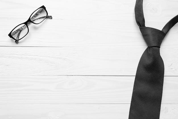 Zwart en wit beeld van mannelijke stropdas en brillen die op een witte houten achtergrond liggen