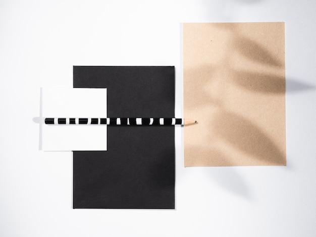 Zwart en wit gestreept potlood op zwart-witte dekens en een bladschaduw op een beige blanco