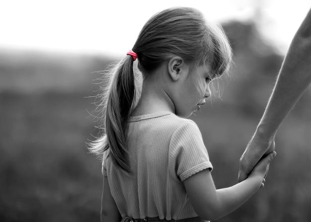 Zwart en wit portret van meisje dat een hand van haar moeder houdt