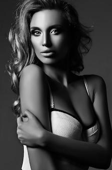 Zwart en wit portret van sensuele glamour mooie blonde vrouw model dame met verse make-up en gezond krullend haar