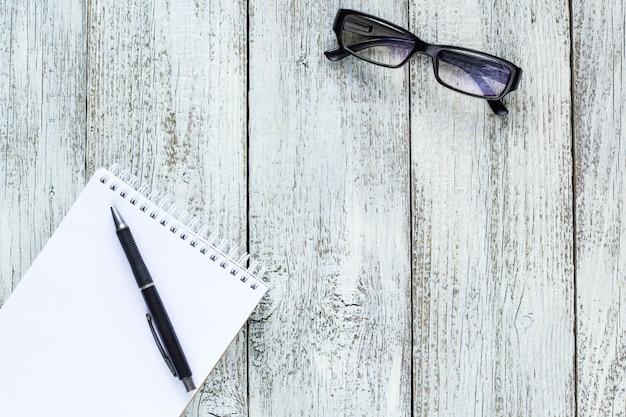 Zwart en wit stilleven: lege kladblok geopend, notitieblokken, pen, bril.