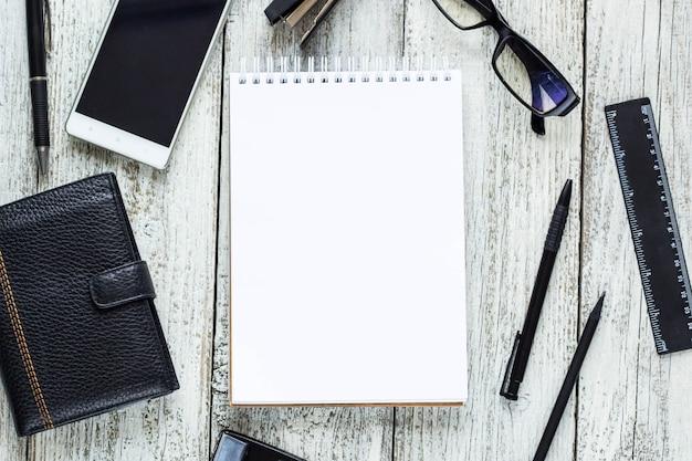 Zwart en wit stilleven: lege kladblok geopend, notitieblokken, pen, potlood, bril, tas.
