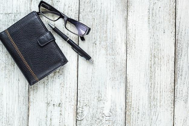 Zwart en wit stilleven: pen, potlood, bril, tas.