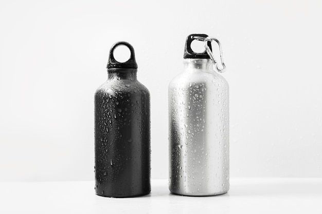 Zwart en zilver, herbruikbare aluminium thermosfles besproeid met water