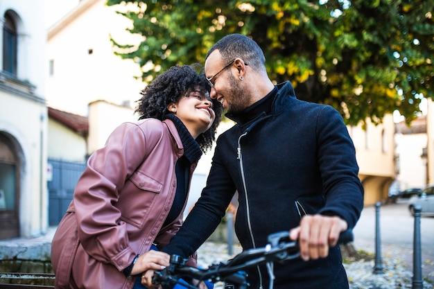 Zwart etnisch paar houdt van elkaar. gelukkige jonge mensen die op fiets zitten.