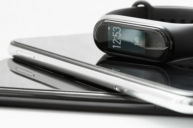 Zwart fitnesshorloge of activity tracker met tijd en stappen op het display. fitness tracker ligt op de smartphones