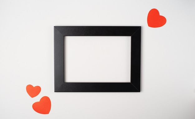 Zwart fotolijstje met rode harten op wit. valentijnsdag concept.