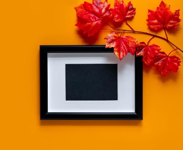Zwart frame met esdoorn takken op oranje achtergrond. herfst concept. plaats voor tekst.