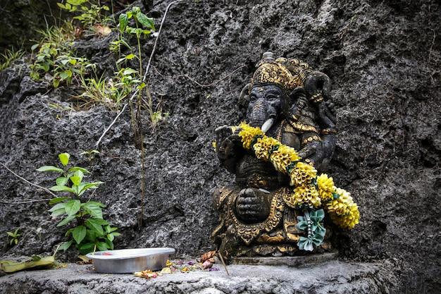 Zwart ganesha-beeld met een krans van bloemen.