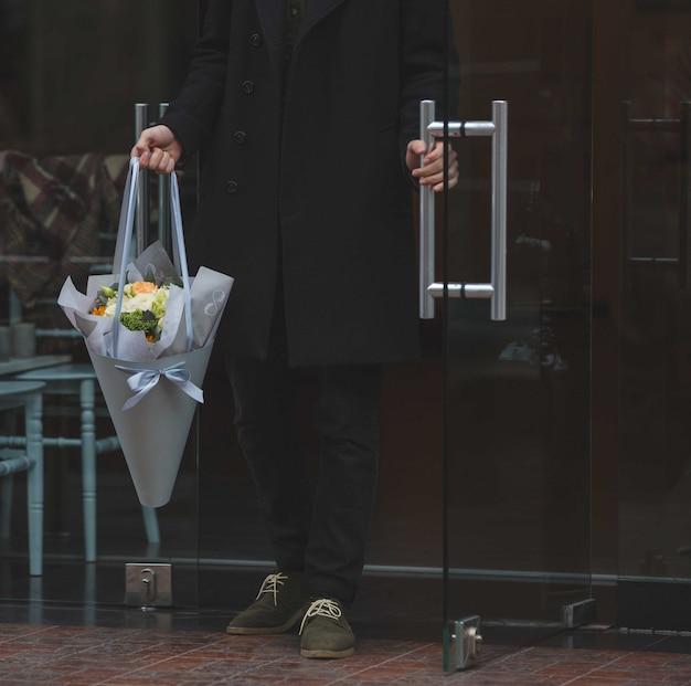 Zwart gekleed man komt binnen met een wit boeket bloemen