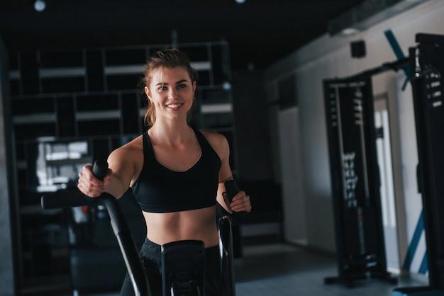 Zwart gekleurde apparatuur. prachtige blonde vrouw in de sportschool tijdens haar weekend