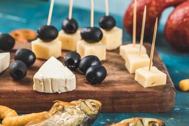 Zwart gemarineerde olijven met verschillende soorten kaas