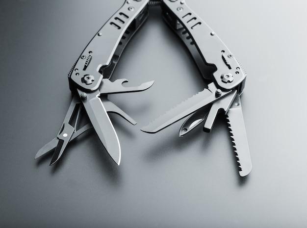 Zwart geopend multitoolmes met diverse tools