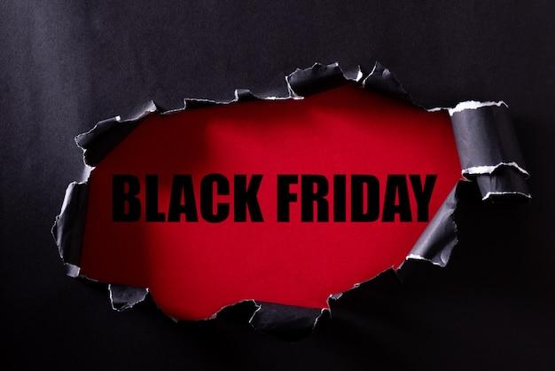 Zwart gescheurd papier en de tekst black friday op een rood.